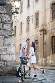 Uomo e donna sono attratti l'uno dall'altro che si baciano vicino alla bici tandem retrò in un ambiente urbano nelle strette stradine