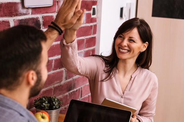 Uomo e donna sorridenti che danno livello cinque in ufficio
