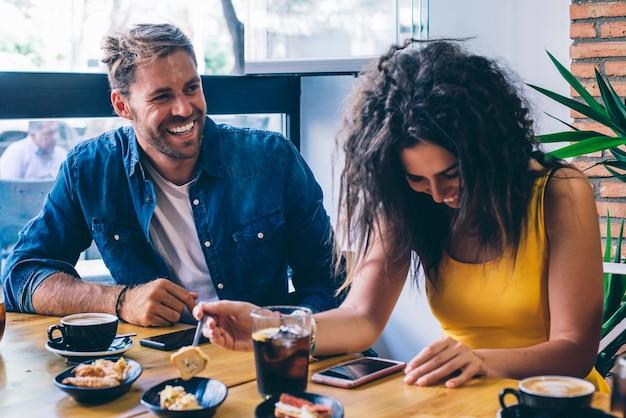 Uomo e donna sorridenti che per mezzo dello smart phone che mangia un caffè
