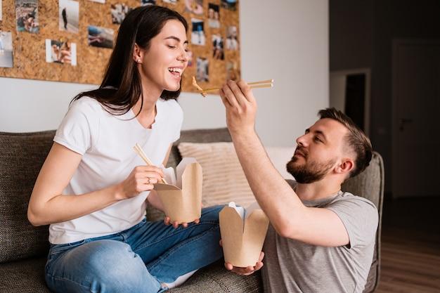 Uomo e donna sorridenti pranzando insieme a casa