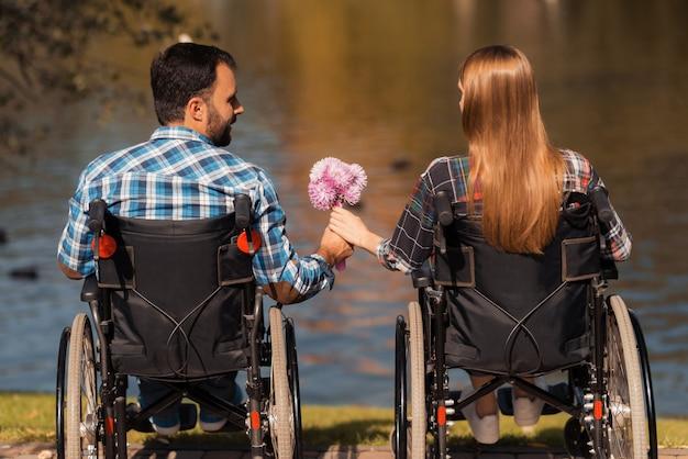 Uomo e donna su sedia a rotelle. concetto di amore