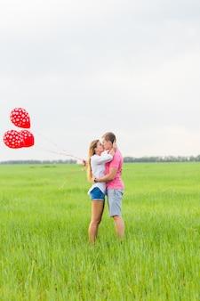 Uomo e donna sul campo con palloncini rossi. coppia felice sulla natura.
