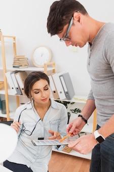 Uomo e donna vestiti casuali che guardano in una lavagna per appunti
