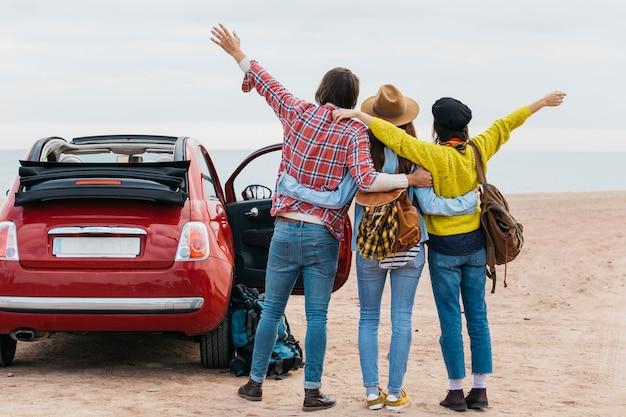 Uomo e donne che si abbracciano vicino auto sulla costa del mare