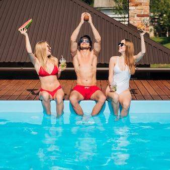 Uomo e donne in posa in costume da bagno