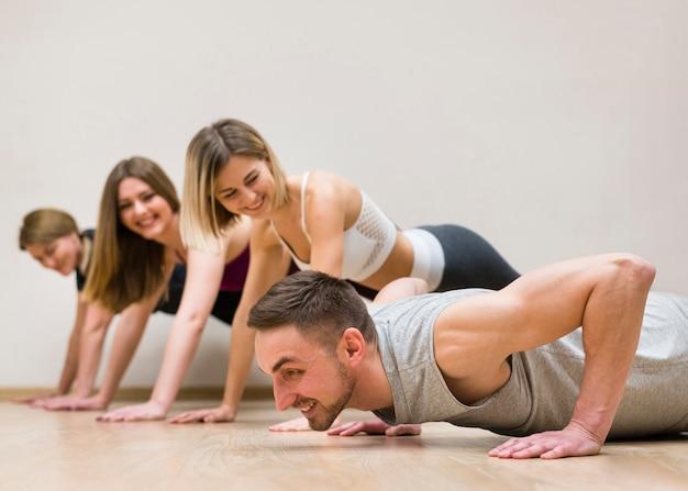 Uomo e gruppo di donne che si allenano insieme