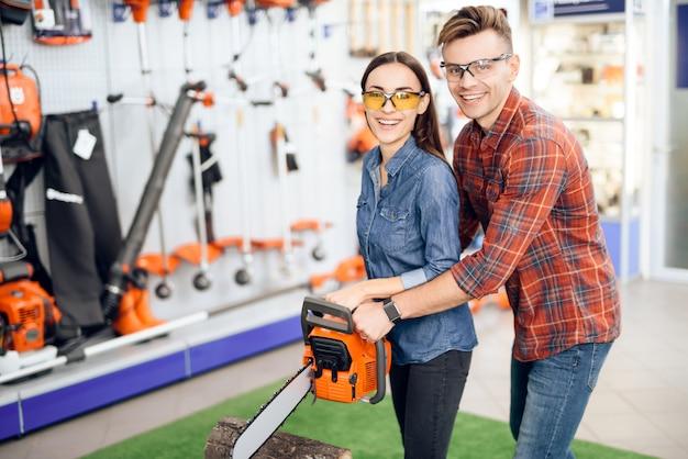 Uomo e ragazza che tengono in mano una motosega.