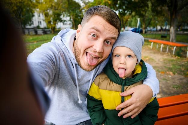 Uomo e ragazzo che prendono un selfie con le lingue fuori