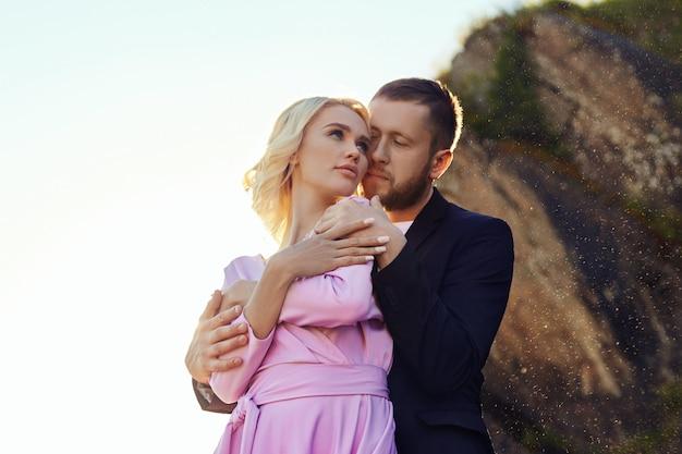 Uomo e una donna che abbraccia in estate al tramonto in bei vestiti. coppia innamorata