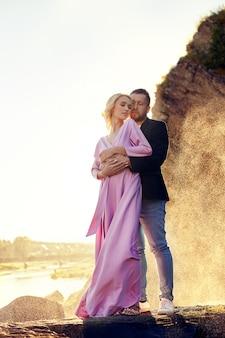 Uomo e una donna che abbraccia in estate al tramonto