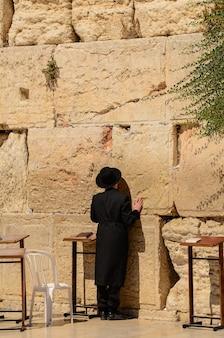 Uomo ebreo ortodosso che prega al muro occidentale a gerusalemme, israele