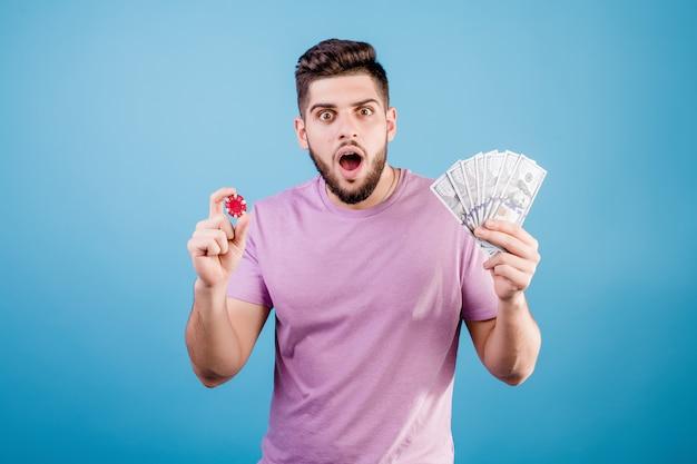 Uomo eccitato con chip di poker da casinò e soldi che ha vinto sul blu