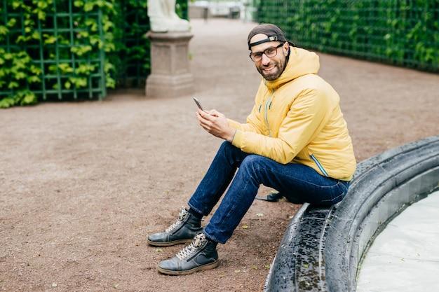Uomo eccitato con la barba e il viso affascinante che indossa abiti alla moda che riposa all'aperto