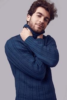 Uomo elegante bello con capelli ricci in maglione blu