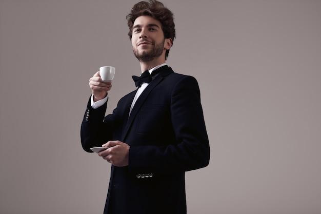 Uomo elegante bello con capelli ricci in smoking che tiene una tazza di caffè espresso