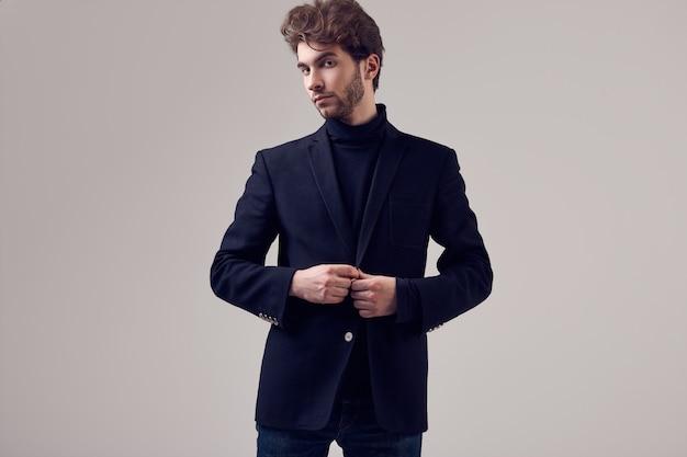 Uomo elegante bello con i capelli ricci che indossa abito e occhiali