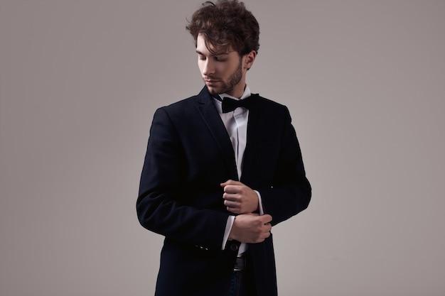 Uomo elegante bello con lo smoking da portare dei capelli ricci