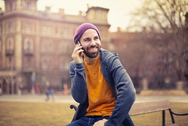 Uomo elegante che parla su uno smartphone