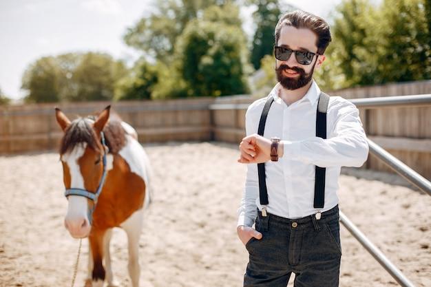 Uomo elegante che sta accanto al cavallo in un ranch