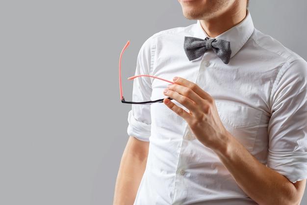 Uomo elegante e alla moda in una camicia bianca con un farfallino con gli occhiali in mano.