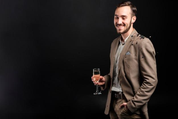 Uomo elegante in posa con un bicchiere di champagne