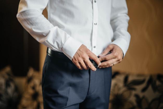 Uomo elegante mette in primo piano cintura di pelle.