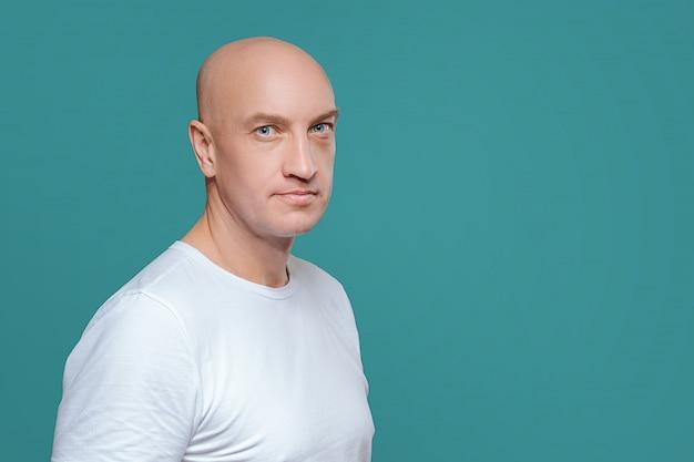 Uomo emotivo in maglietta bianca con espressione facciale arrabbiata su fondo