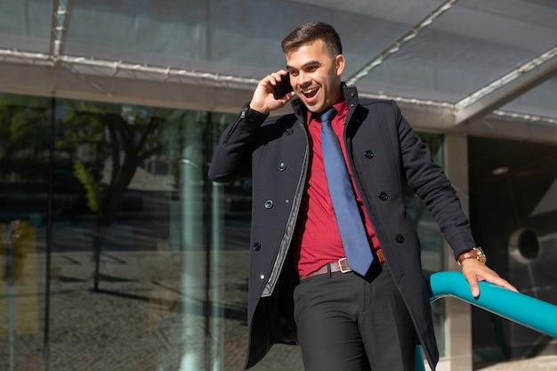 Uomo emozionante allegro che comunica sul telefono e che si muove giù dalle scale