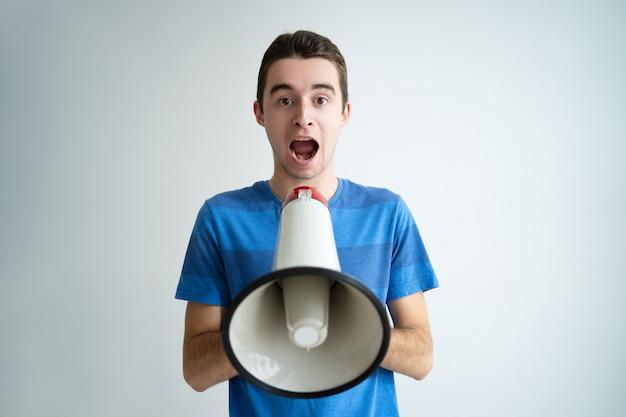 Uomo emozionante che tiene il megafono e che grida forte