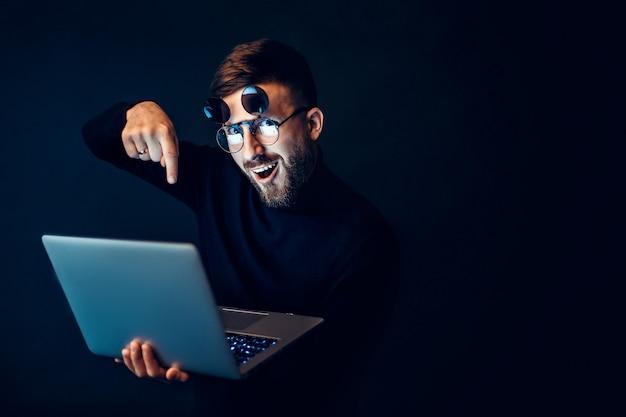 Uomo emozionante in vetri che tengono computer portatile