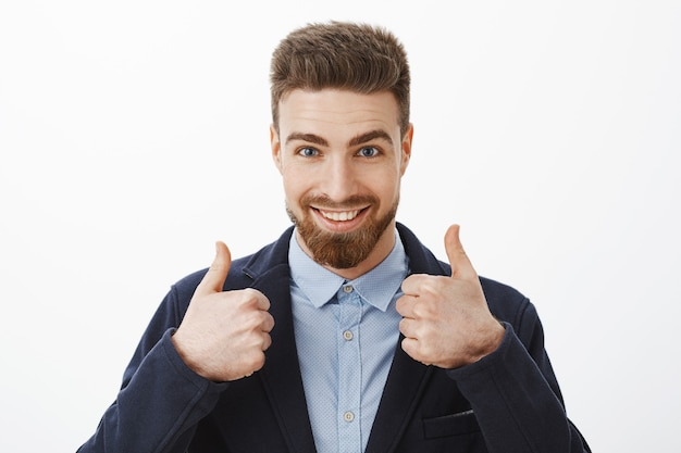 Uomo energico di bell'aspetto e di sicuro successo con barba e occhi azzurri in elegante abito formale che mostra i pollici in su essendo assicurato il piano funziona alla grande, sicuro di sé contro il muro grigio