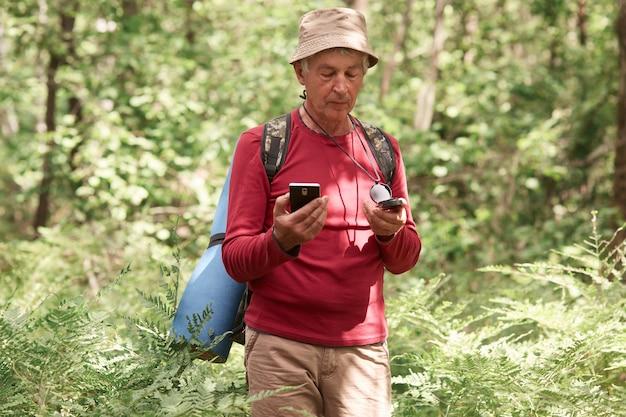 Uomo entusiasta serio che vaga nella foresta, con bussola e smartphone in mano, scegliendo il suo itinerario di viaggio