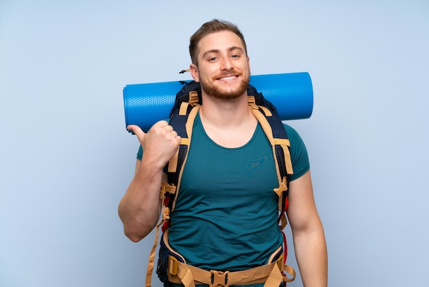 Uomo escursionista sul muro blu che punta verso il lato per presentare un prodotto