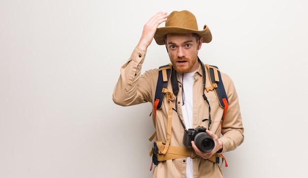 Uomo esploratore giovane rossa preoccupato e sopraffatto. in possesso di una macchina fotografica.