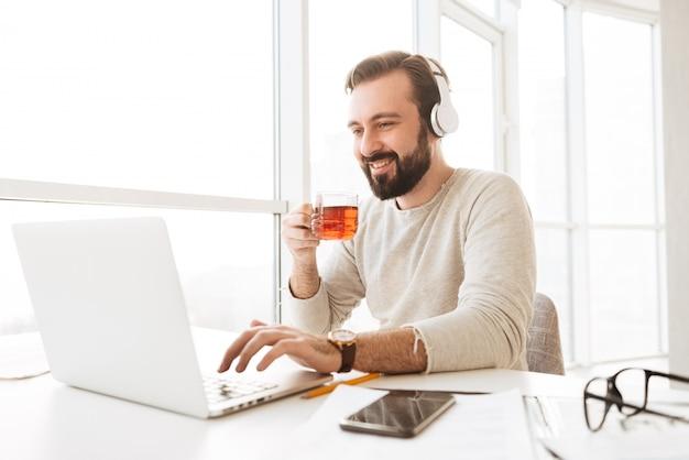 Uomo europeo gioioso con capelli castani corti che beve tè e ascolta la musica tramite cuffie wireless, mentre si utilizza il notebook