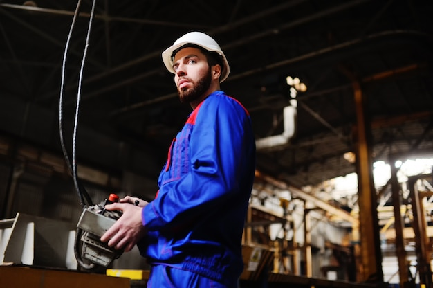 Uomo, fabbrica, telecomando in mano