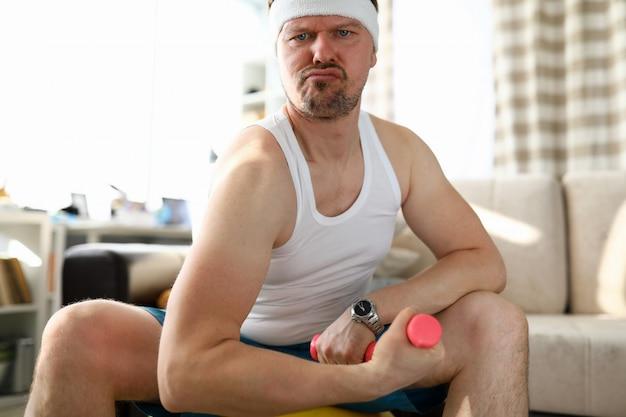 Uomo facente smorfie divertente che si siede sulla palla adatta che risolve con le piccole teste di legno rosa a casa durante il ritratto di periodo di quarantena del coronavirus
