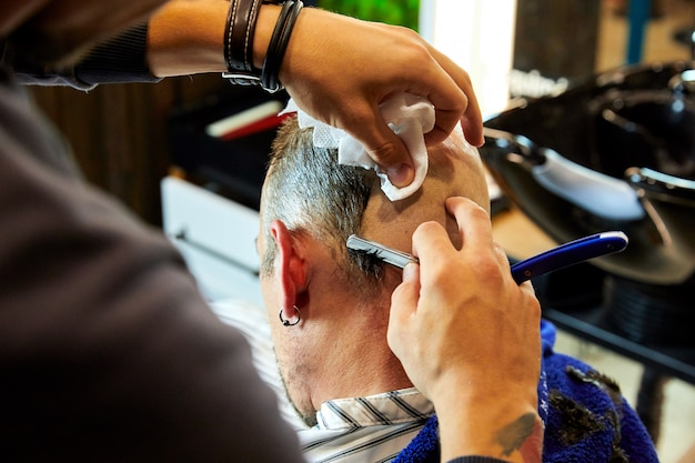 Uomo farsi radere con un rasoio da parrucchiere presso il barbiere