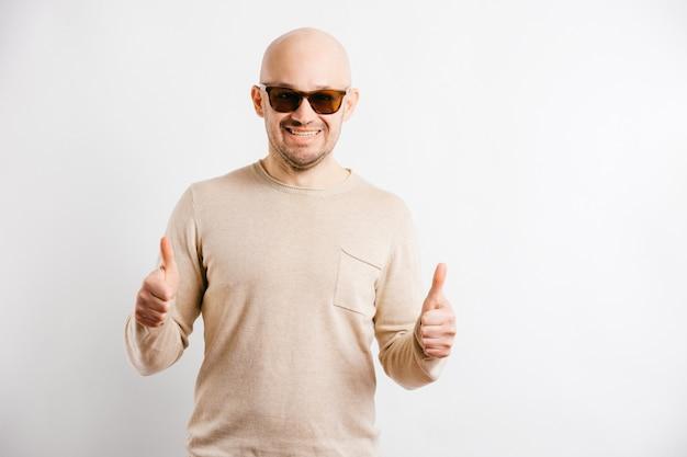 Uomo felice adulto in occhiali da sole che mostra i pollici in su