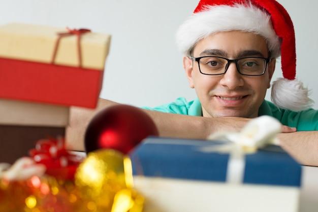Uomo felice al tavolo con regali di natale e palline