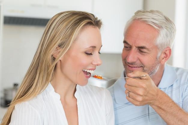 Uomo felice che alimenta al suo compagno un cucchiaio di verdure