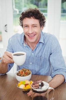 Uomo felice che beve tè dal tavolo