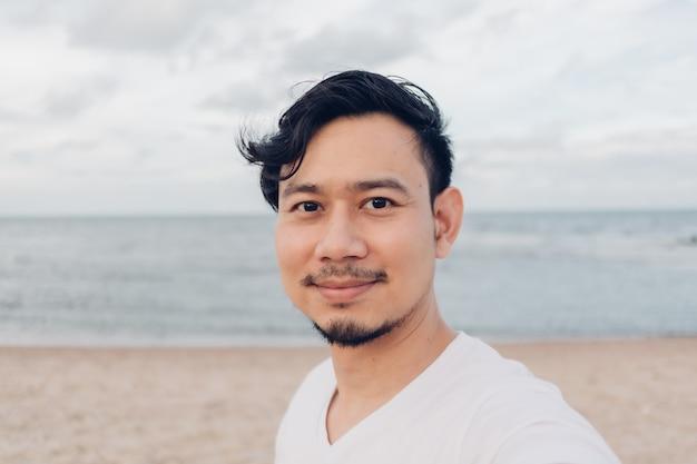 Uomo felice che cattura selfie mentre si cammina sulla spiaggia