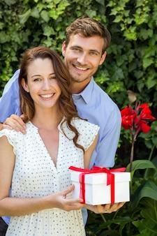 Uomo felice che dà regalo alla donna all'iarda anteriore
