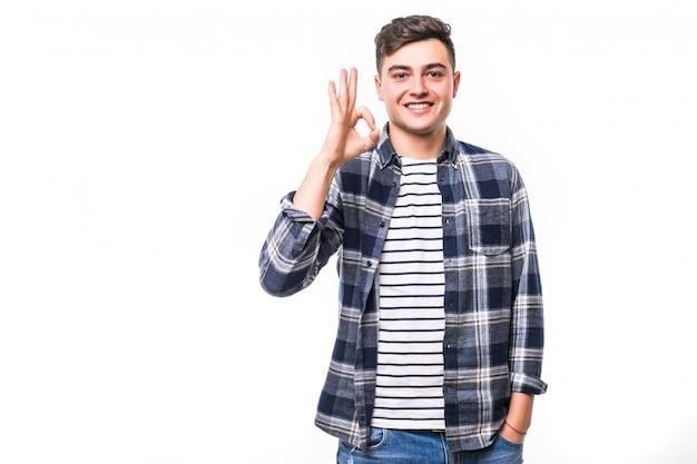 Uomo felice che dà segno giusto davanti al muro bianco