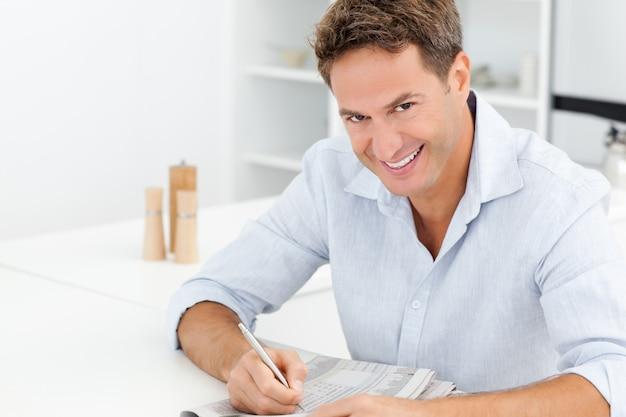 Uomo felice che fa un cruciverba che si siede ad una tabella