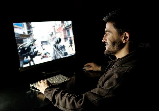 Uomo felice che gioca videogioco sul desktop computer