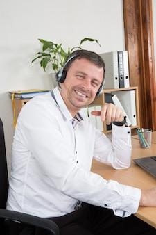 Uomo felice che lavora al callcenter, utilizzando l'auricolare