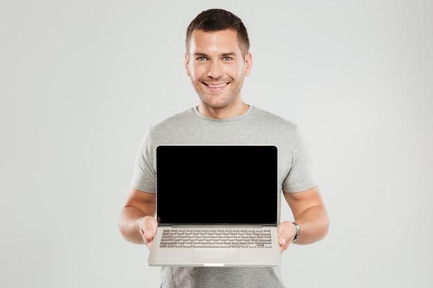 Uomo felice che mostra esposizione del computer portatile.