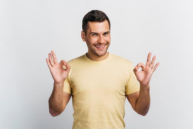 Uomo felice che mostra segno giusto